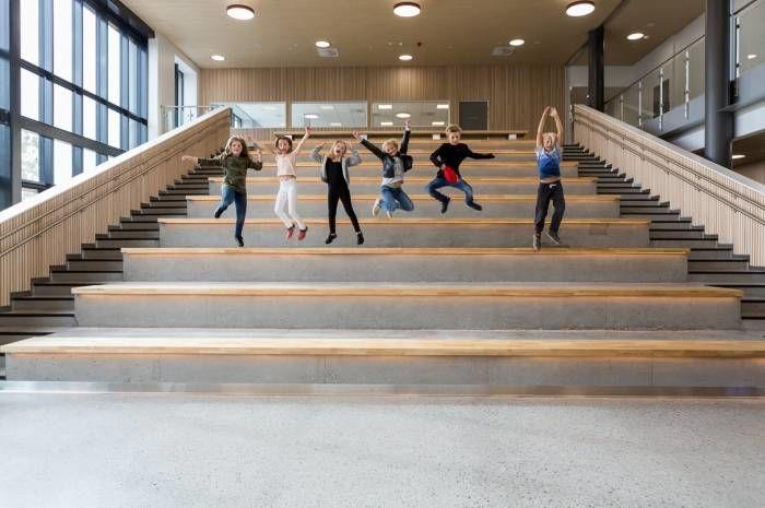 Sammen med småhus og boligblokker er skolebygg blant byggene som bruker minst energi. Bildet viser hoppende glade barn på Brynseng skole, som er en nær-nullenergiskole. Foto: Tove Lauluten